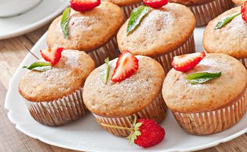 Strawberry muffin on a white plate with a fresh strawberry
